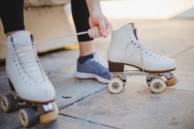 Mulher sentada laçando patins