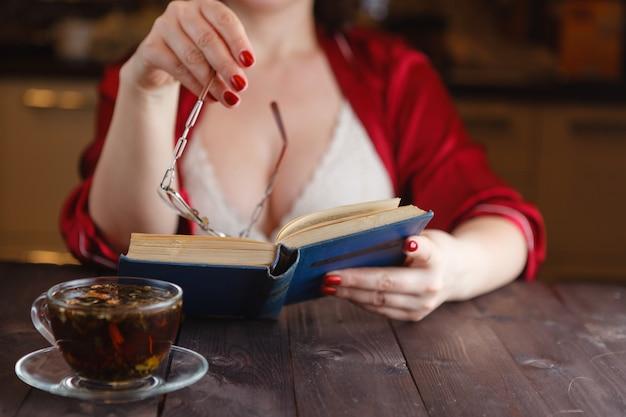Mulher sentada lendo livro e beber chá