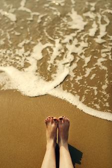 Mulher sentada na areia da praia