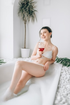 Mulher sentada na banheira com uma taça de vinho