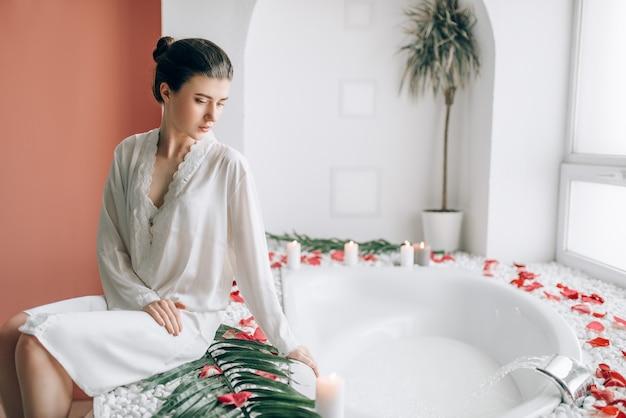 Mulher sentada na banheira decorada com pétalas de rosa