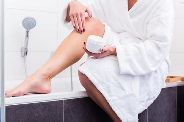Mulher sentada na beira da banheira colocando loção nas pernas
