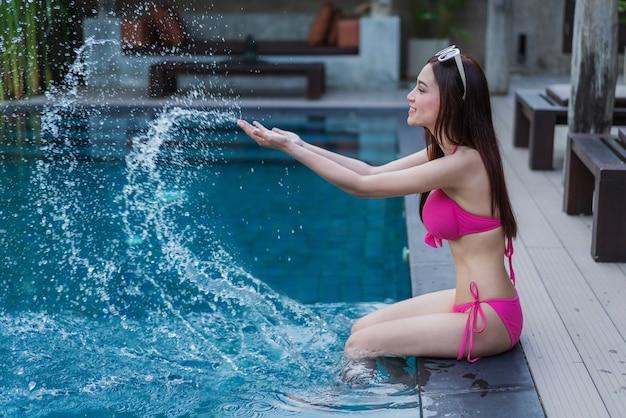 Mulher sentada na beira da piscina