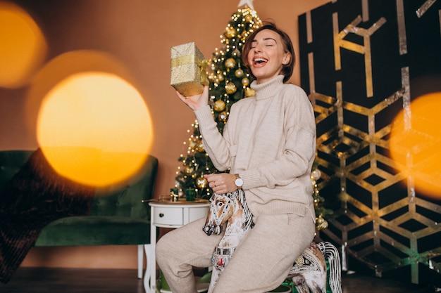 Mulher sentada na cadeira de pônei de madeira perto da árvore de natal
