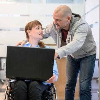 Mulher sentada na cadeira de rodas e amigo