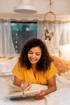 Mulher sentada na cama a ler de frente
