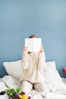 Mulher sentada na cama de pijama cobrindo o rosto com um livro
