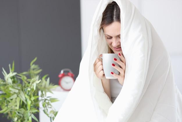 Mulher sentada na cama, debaixo das cobertas, bebendo chá. conceito de café da manhã na cama