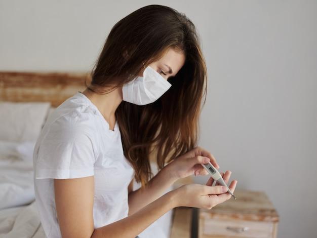 Mulher sentada na cama do quarto sem um termômetro nas mãos verificando a temperatura