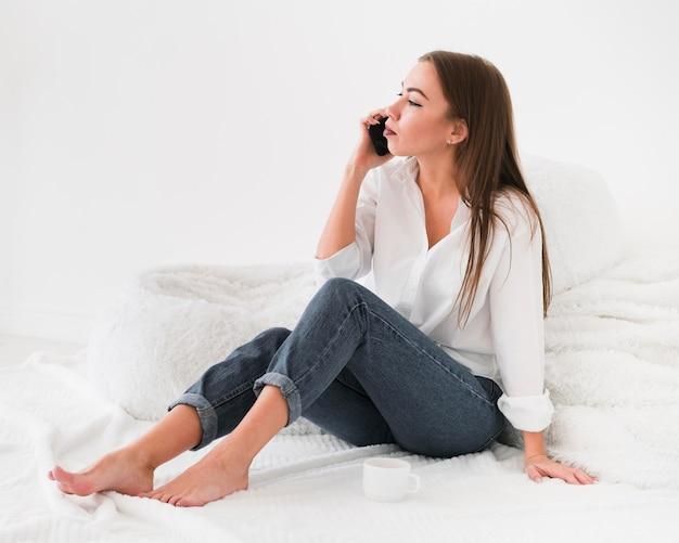 Mulher sentada na cama e falando ao telefone