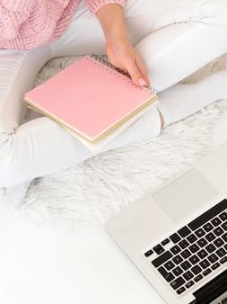 Mulher sentada na cama e segurando um bloco de notas