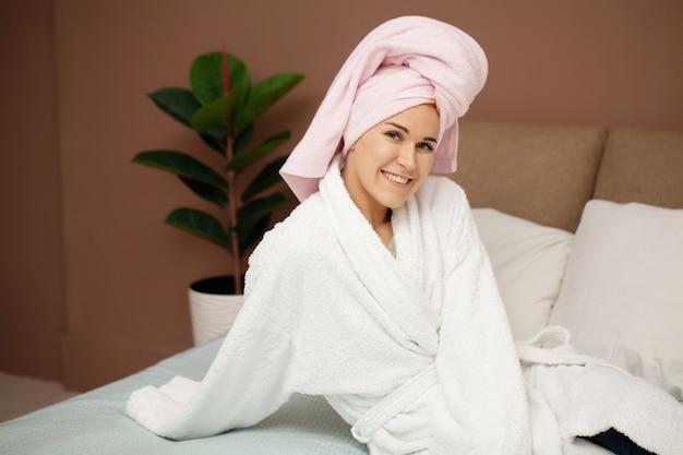 Mulher sentada na cama, fazendo tratamentos de spa