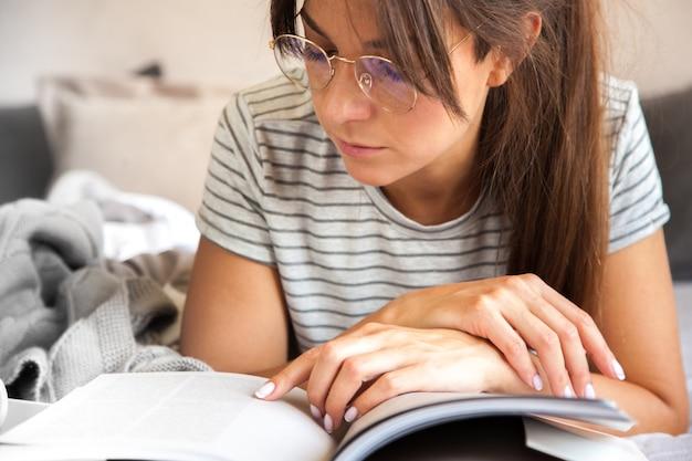 Mulher sentada na cama lendo um livro e tomando café da manhã.
