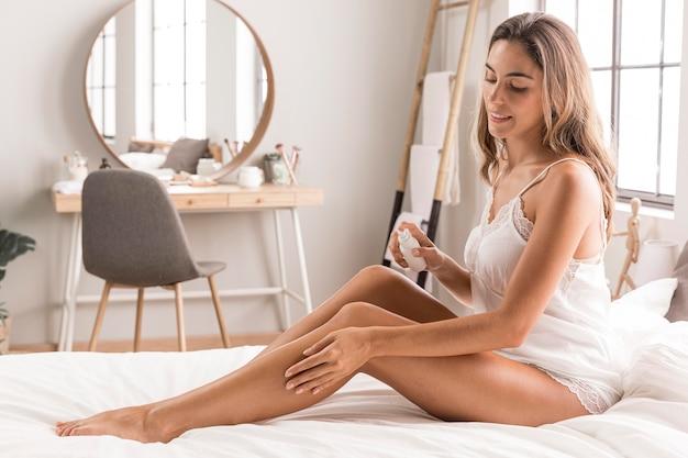 Mulher sentada na cama massageando as pernas