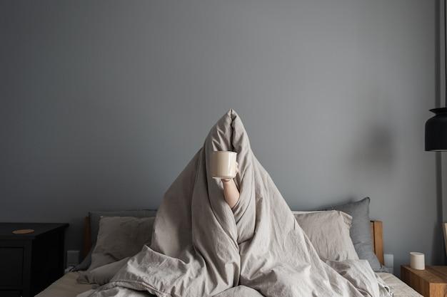 Mulher sentada na cama, segurando uma caneca com café na mão