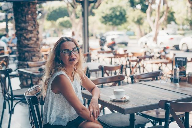 Mulher sentada na camisa branca texturizada no terraço do café durante o dia.