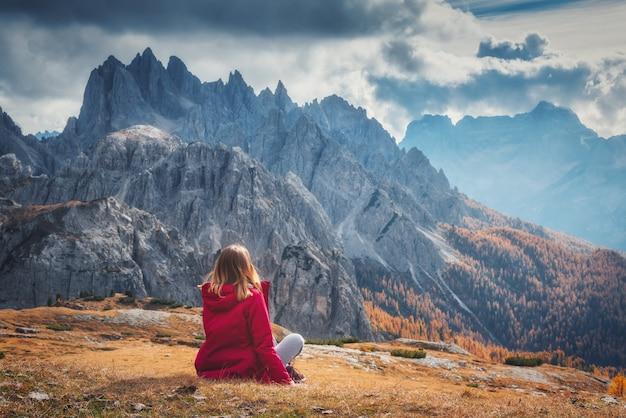 Mulher sentada na colina contra as dolomitas