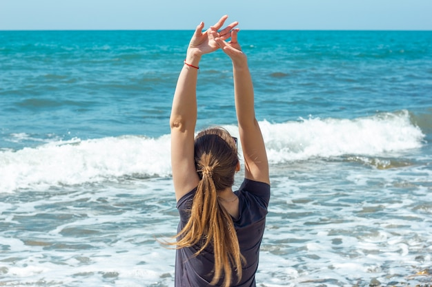 Mulher sentada na costa levantando as mãos