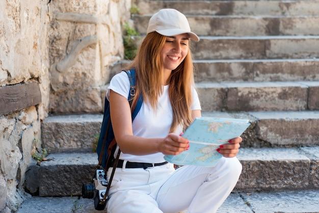 Mulher sentada na escada ao ar livre com um mapa