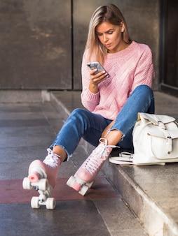 Mulher sentada na escada com patins e olhando para smartphone
