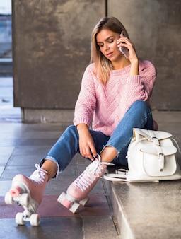 Mulher sentada na escada com patins e smartphone