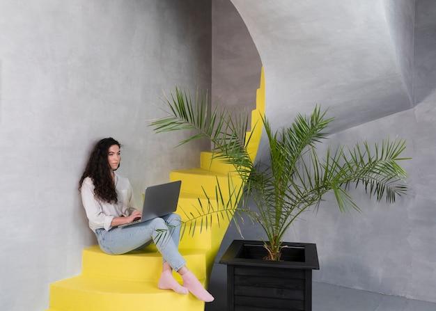 Mulher sentada na escada usando o laptop