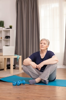 Mulher sentada na esteira de ioga esperando o treinador de bem-estar