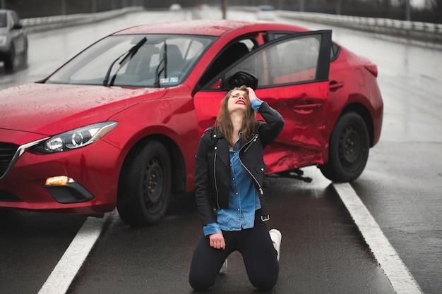 Mulher sentada na estrada após um acidente. mulher ferida se sentindo mal após um acidente de carro