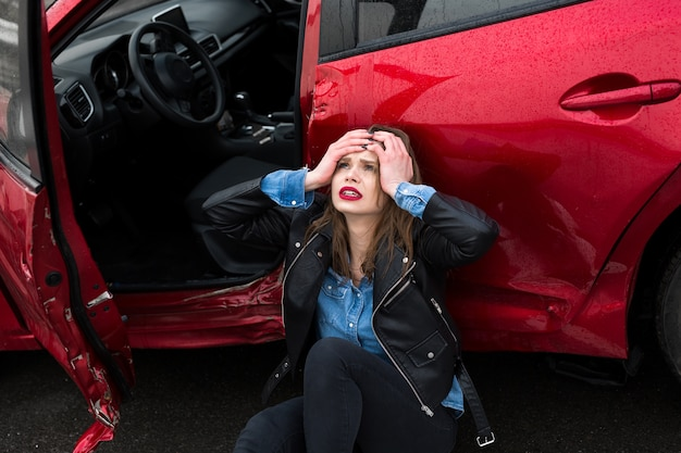 Mulher sentada na estrada após um acidente