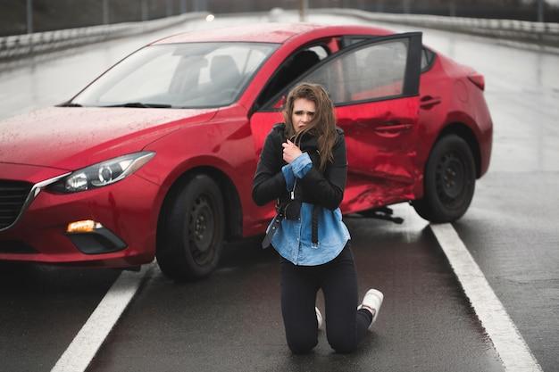 Mulher sentada na estrada após um acidente.