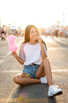 Mulher sentada na estrada comendo algodão doce