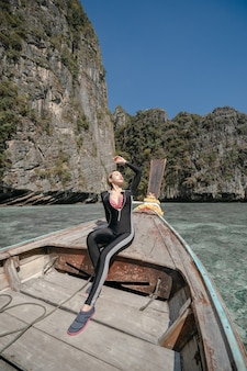 Mulher sentada na frente de um barco longtail no mar no mar de andaman da lagoa de pileh, ilhas phi phi, tailândia.
