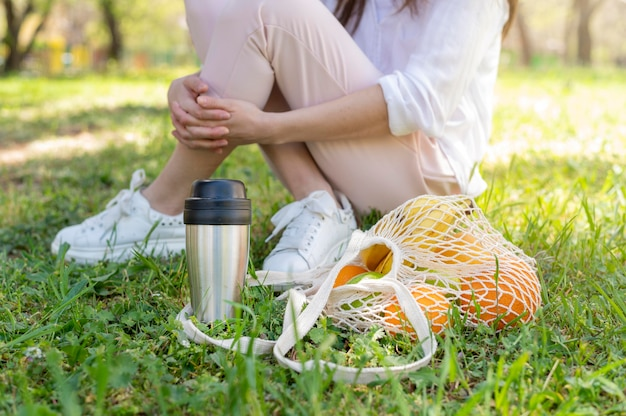 Mulher sentada na grama com saco reutilizável e garrafa térmica