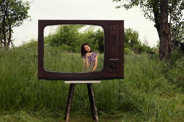 Mulher sentada na grama do jardim, dentro da velha moldura da televisão vintage, tecnologia moderna e saúde mental