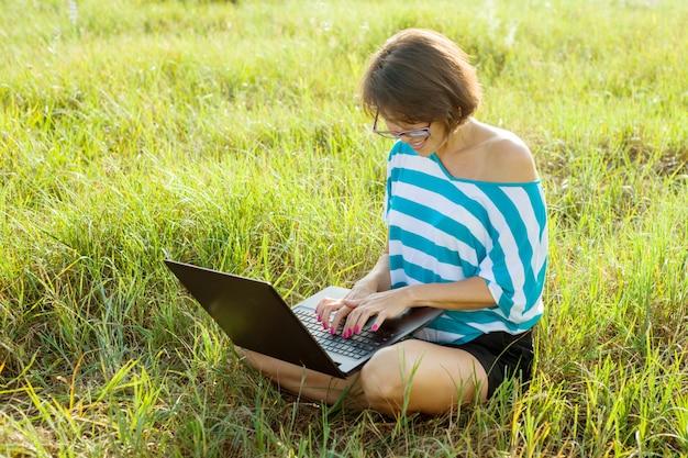 Mulher sentada na grama e trabalhando no laptop