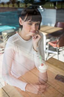 Mulher sentada na lanchonete com milk-shake na mesa
