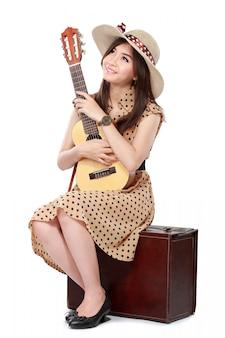 Mulher sentada na mala dela enquanto toca guitarra