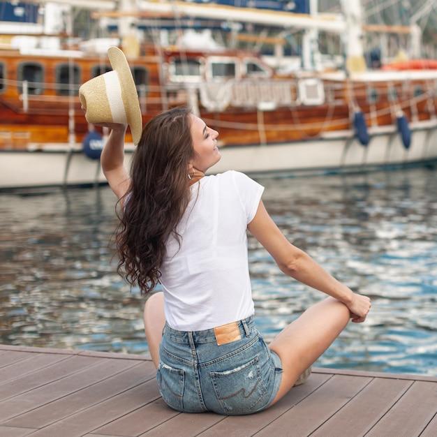 Mulher sentada na margem de um porto