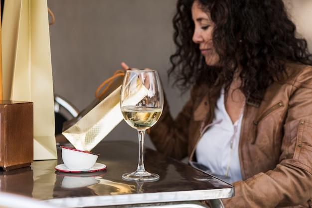 Mulher sentada na mesa com copo de vinho
