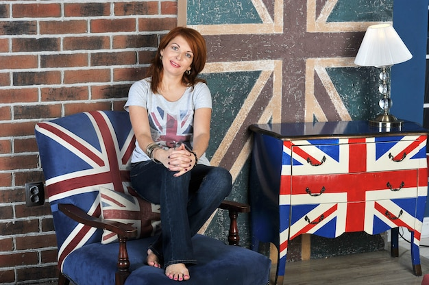 Mulher sentada na mesa de cabeceira na bandeira inglesa