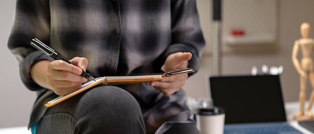 Mulher sentada na mesa de trabalho e tomar nota no livro de agenda