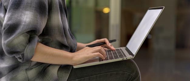 Mulher sentada na mesa enquanto trabalhava com laptop mock-up