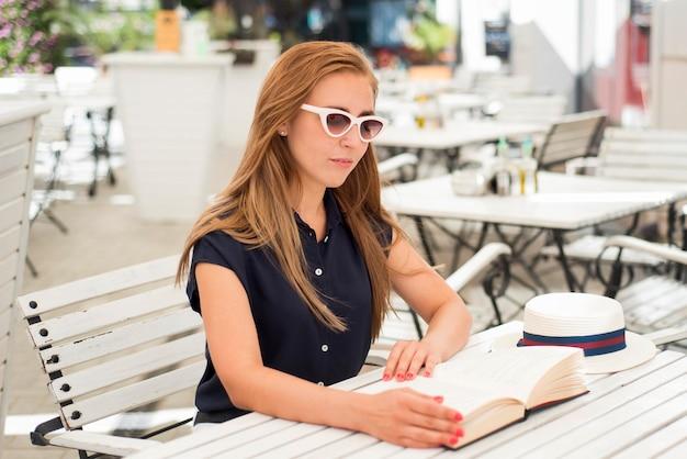 Mulher sentada na mesa lendo livro