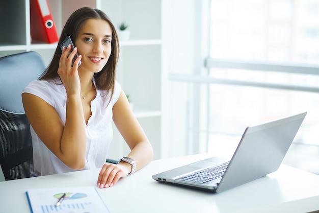 Mulher sentada na mesa, trabalhando no laptop no escritório moderno