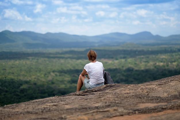 Mulher sentada na montanha