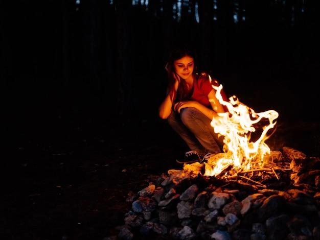 Mulher sentada na natureza perto da fogueira da floresta