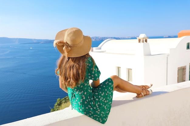 Mulher sentada na parede olhando para uma vista deslumbrante do mar mediterrâneo