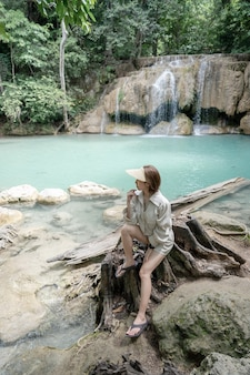 Mulher sentada na pedra na cachoeira erawan no parque nacional kanchanaburi tailândia