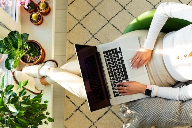 Mulher sentada na poltrona e colocando os pés no parapeito da janela com plantas domésticas em um vaso de flores, trabalha no laptop em casa durante o auto-isolamento. negócios em casa. vista do topo.