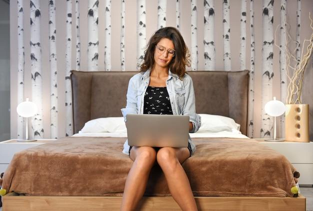 Mulher sentada na ponta da cama, trabalhando em um laptop em casa